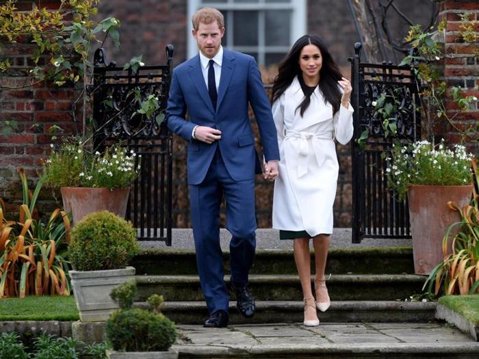 Il principe Harry e Meghan Markle raggiungono i fotografi per le prime foto ufficiali da fidanzati. Il giardino scelto è quello di Kensington Palace